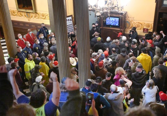Protestors let out a cheer as they watch the proceedings on a monitor outside the House of Representatives inside the Capitol in Lansing.  The Michigan House approved a resolution that authorizes Speaker Lee Chatfield, R-Levering, to file a legal challenge against unilateral efforts Gov. Gretchen Whitmer has taken to prevent the spread of COVID-19.