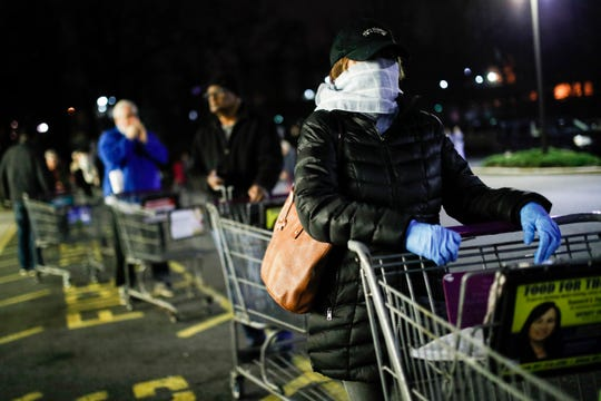 FILE- In this March 20, 2020 file photo customers wearing protective masks and gloves wait in line at a Stop & Shop supermarket in Teaneck, N.J., that opened special morning hours to serve people 60-years and older due to coronavirus concerns.