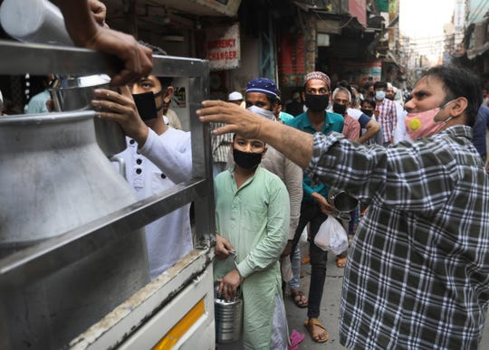 Indian Muslims queue up to buy milk during a three hour relaxation of restrictions to buy essential items during the holy month of Ramadan at the old quarters of New Delhi, India, Saturday, April 25, 2020.