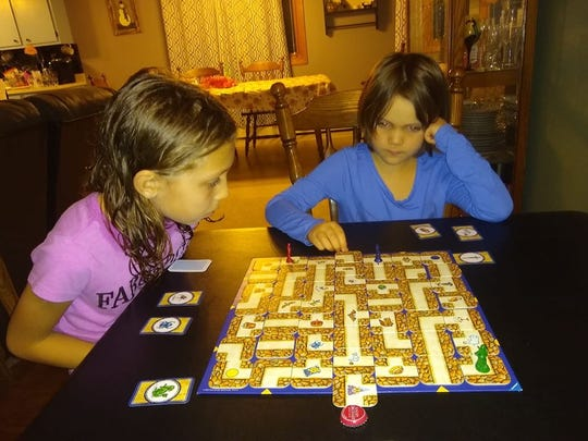 Lily and Luna Miller focus as Luna makes a move in Labyrinth. Their dad, Ross Miller,  find that the cost per game is often well balanced by the amount of play time they get out of each one.