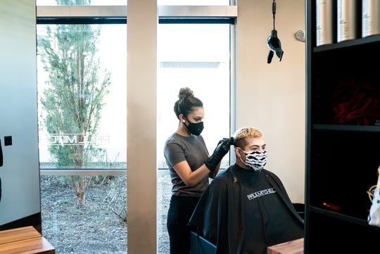 """Stylists at Studio Be Salon practice cutting each other's hair Wednesday, April 29, 2020, while wearing masks and following other state and county rules and guidelines for reopening May 1 as Colorado transitions from a """"stay-at-home"""" to """"safer-at-home"""" order."""