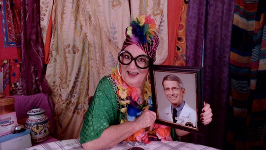 Betsy Bennett, as Naomi Lipschitz-Yamamoto-Murphy, poses with a photo of her beloved Dr. Fauci.