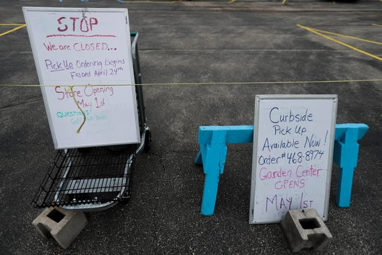 Curbside pickup signs offer instructions for shoppers earlier this season at Larry's Bellevue Gardens. The greenhouse opened Friday.