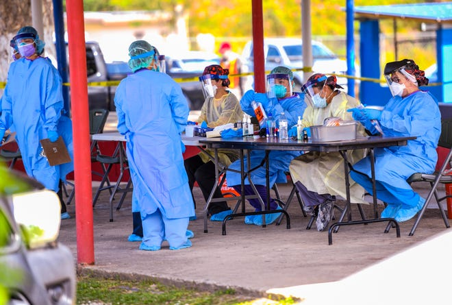 Department of Public Health and Social Services nurses prepare test kits for resident testing at a drive-through outreach program in this file photo from April 30 near the Mangilao Senior Center.