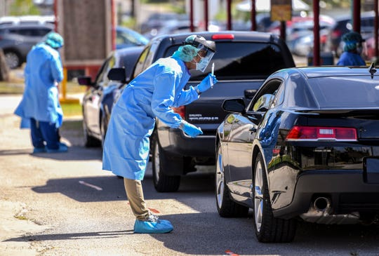 A Department of Public Health and Social Services nurse describes to a driver the process of a nasal swab as he and other health professional test for the coronavirus, or COVID-19, during a drive-thru testing near the Mangilao Senior Center on Thursday, April 30, 2020.