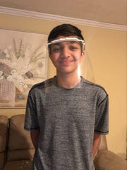 Henderson resident Shaurya Jadhav, 15, poses with a face shield he made using a 3D printer.