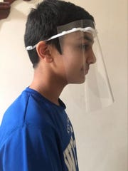 Shaurya Jadhav, 15, Henderson, poses with one of the face shields he printed for medical workers here and in Boston and New York.