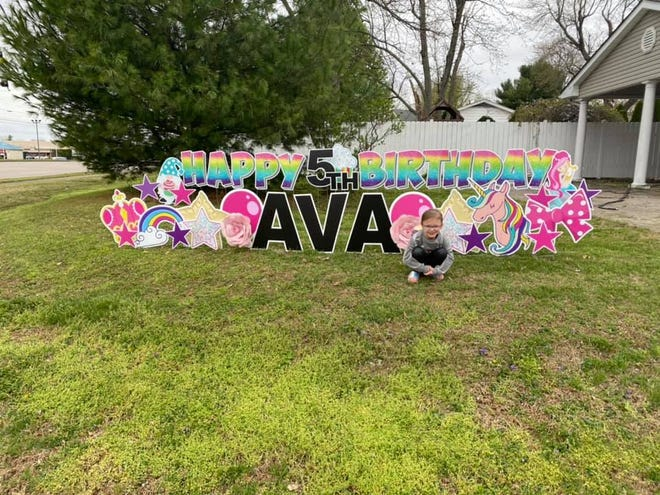 """Five-year-old Ava, daughter of Katie Giles, poses with the yard sign that was a centerpiece of her birthday celebration. """"We had people lining up down our road almost an hour before scheduled time! It included friends but also people I would have never thought actually cared,"""" wrote Katie."""