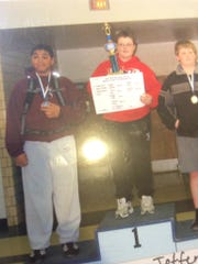 Aaron Costello, center, stands with a trophy after winning a youth wrestling tournament. Tristan Wirfs, left, was in the same tournament. Both grew up to be Hawkeyes.