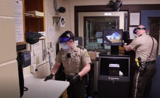 An image taken from a video produced by the Johnson County Sheriff's Office shows deputies disinfecting equipment in the facility during the COVID-19 pandemic in Iowa City.