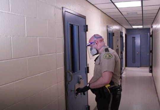 An image from a video produced by the Johnson County Sheriff's Office shows a deputy wearing personal protective equipment during the COVID-19 pandemic in Iowa City.