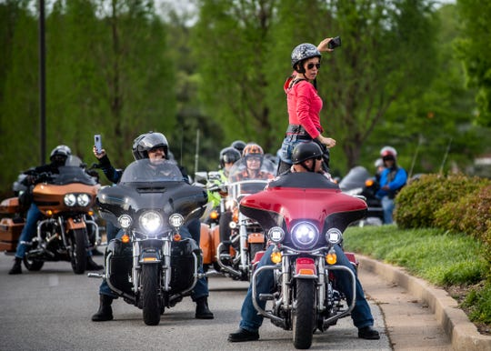 Amber Thompson signals the motorcyclists to rev their engines while she holds her cellphone to show their support to all the health care workers in West Tennessee, in Jackson, Tenn, Tuesday, April 28, 2020. The motorcyclists rode a lap at local hospitals and donated food.