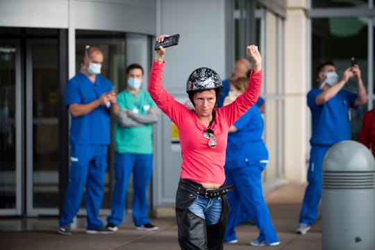 Amanda Thompson signals the motorcyclists to rev their engines to show their support to all the health care workers in West Tennessee, in Jackson, Tenn., Tuesday, April 28, 2020. The motorcyclists rode a lap at local hospitals and donated food.