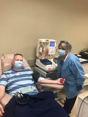 Todd Lewis smiles through his mask as he donates plasma on Thursday at Lifeline Blood Services in North Jackson.
