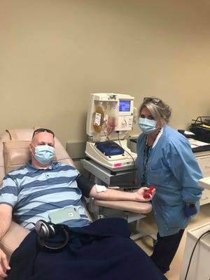Todd Lewis smiles through his mask as he donates plasma on Thursday at Lifeline Blood Services in North Jackson.