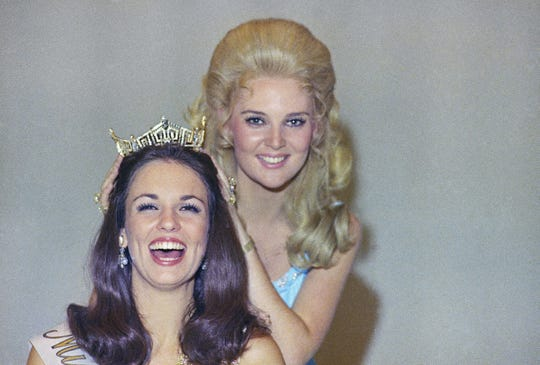 Phyllis George, the former Miss Texas won the national title of Miss America in Atlantic City on Sept. 12, 1970, having the crown placed on her head by the former Miss America, Pamela Anne Eldred of Michigan. (AP Photo)