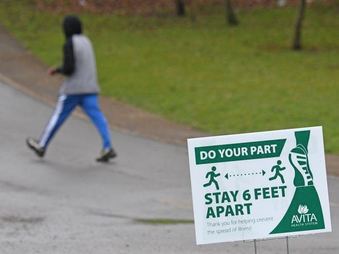 A pedestrian walks by a sign from Avita Health System encouraging social distancing on Thursday at North Lake Park.