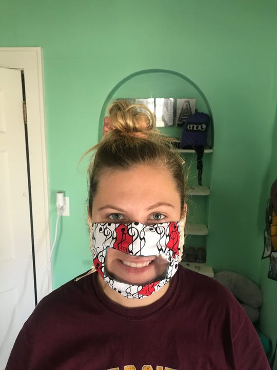 Anna Baish shows off one of the see-through masks that Vicki Spiering made to help people who have hearing difficulties see facial expressions. Baish's mother, Lizabeth, works as a program coordinator at HEARWisconsin, anonprofit that helps infants, children and adults with hearing loss.