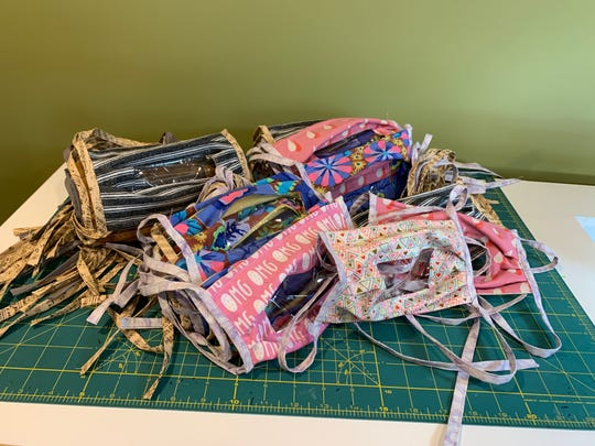 Vicki Spiering of Wauwatosa uses cloth and colorful designs for many of the see-through masks, which she makes in her basement.