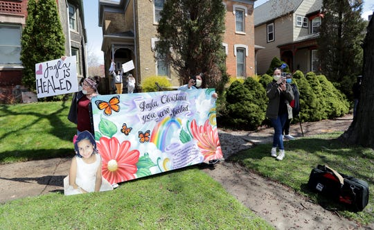 Elva Gonzalez, far left, cousin of Jayla Christina Rodriguez, holds a sign with other family members of Jayla as a parade travels past Jayla's home.