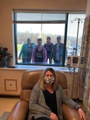 Stephanie Erwin, Jennifer McGowan, Jennifer Alspaugh and Brian Blackford all stand behind Jennifer Blackford as she receives her first chemo treatment