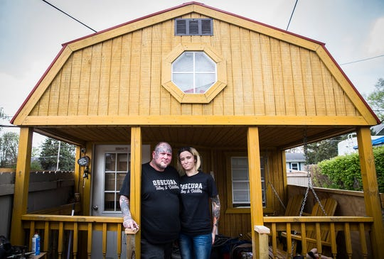 Ashley and Mitch Campbell stand on the porch of their tiny home which is positioned in the parking lot at Obscura Tattoo and Oddities April 29, 2020.