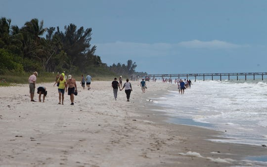 Beach goers enjoy a stroll along the shores of Naples Beach, Thursday, April 30, 2020. The City of Naples reopened to the beaches to the public on Thursday.