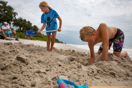 From left, Kylie Condon, 10, and her brother Jack Condon 11, both from Lafayette Hill, Pennsylvania, play in the sad, Thursday, April 30, 2020, at Naples Beach.