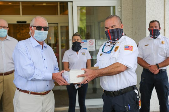 Jamie Gibbs, president of the Port Royal Property Owners Association, presents Deputy  Chief Jerry Picar with gift cards from local restaurants to be distributed to police officers in Naples.