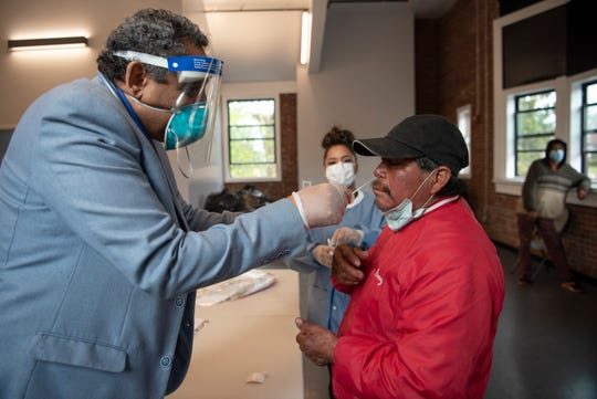 Dr. Gammal Hassanien administers a coronavirus test to a Passaic homeless man at the Dignity House on April 30, 2020. Passaic Mayor Hector Lora organized the free coronavirus testing and showers for the city homeless.