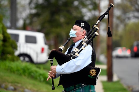 Doug Parody of Midland Park plays the bag pipe as family and friends drive by the home of Anne Coughlan (not pictured) for her 71st birthday on Thursday, April 30, 2020, in Fair Lawn.