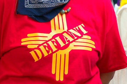 """In this Tuesday, April 28, 2020, still image taken from video, a resident in Grants, N.M. wears a """"defiant"""" T-shirt with a New Mexico Zia symbol in support of the city's mayor who allowed small businesses to reopen this week in defiance of Gov. Michelle Lujan Grisham's statewide health order over COVID-19."""