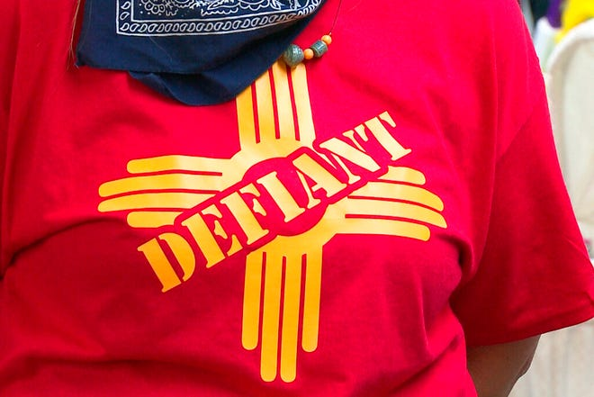 "In this Tuesday, April 28, 2020, still image taken from video, a resident in Grants, N.M. wears a ""defiant"" T-shirt with a New Mexico Zia symbol in support of the city's mayor who allowed small businesses to reopen this week in defiance of Gov. Michelle Lujan Grisham's statewide health order over COVID-19."
