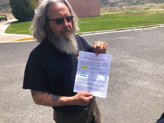 """Grants, New Mexico Mayor Martin """"Modey"""" Hicks holds a warning issued by New Mexico State Police as the city-owned golf course in Grants continued to operate Monday, April 27, 2020, despite a public health order that shuttered nonessential businesses to prevent the spread of COVID-19."""