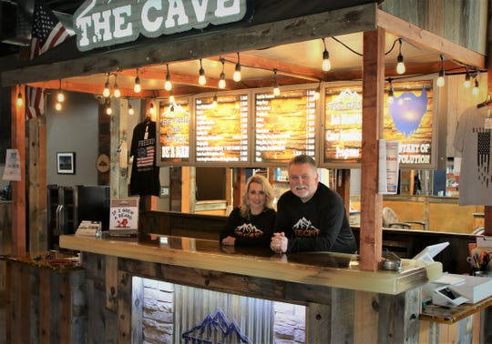 Brandy and Martin Caddell, owners of The Cave Men's Grooming, lean against the front counter of their Farmington business, which has been closed for the past several weeks because of the COVID-19 shutdown.