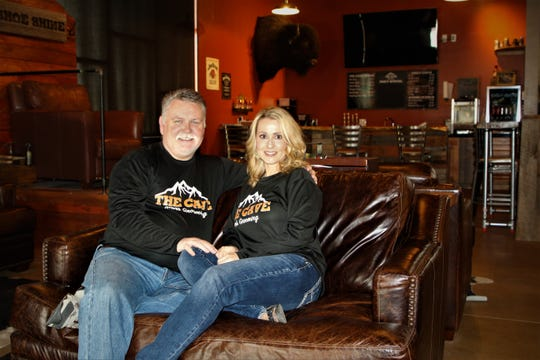 Owners Martin and Brandy Caddell relax inside The Cave Men's Grooming in Farmington.