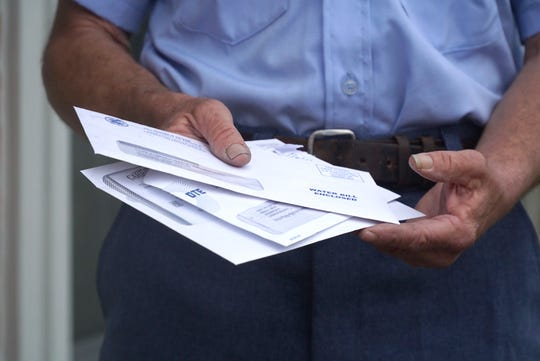 Ron Bruff handles some letters outside a Livonia home.