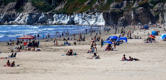 In this Saturday, April 25, 2020, file photo, people gather on the beach in Pismo Beach, Calif., on the state's Central Coast. A memo sent to California police chiefs says Gov. Gavin Newsom will order all beaches and state parks closed starting Friday, May 1, to curb the spread of the coronavirus.