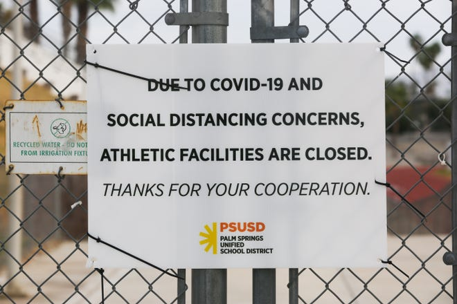 A sign sits outside of Palm Springs High School football field stating the stadium is closed during the coronavirus pandemic on Thursday, April 30, 2020 in Palm Springs, Calif.