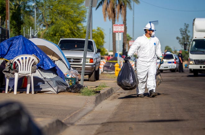 City of Phoenix workers conduct a cleaning of an encampment of people experiencing homelessness south of downtown Phoenix during the novel coronavirus pandemic on April 29, 2020.