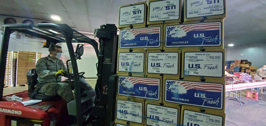 Arizona National Guard help sort produce at the Nogales food bank. The food bank has given out at least 3,100 boxes in the past two weeks.