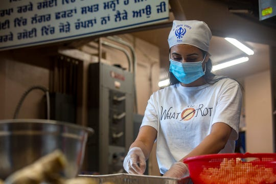 Pawan Kaur prepares dishes to-go at the Gurdwara Dasmesh Darbar in Salem, on April 30, 2020. Over 1,000 meals have been prepared and delivered by the Sikh temple community to Salem Hospital employees during COVID-19.