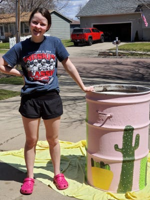 Delaney Kiesow stands next to her contribution of the Brandon Parks and Rec garbage can painting program.