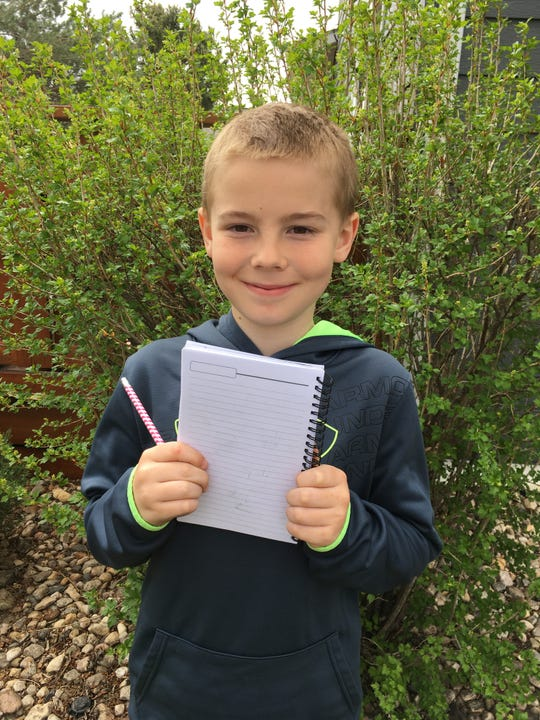 William Korman, 9, holds a notebook for his comic ideas.