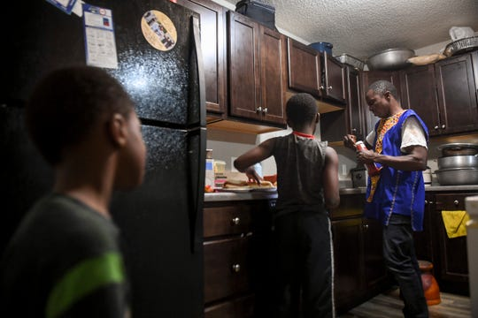 John Deranamie cooks dinner for his sons, Shadrach Cole, 4, and Joel Cole, 9, on Wednesday, April 29, 2020 at his home in Sioux Falls, S.D.