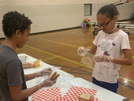 Children in the Waynesboro YMCA's childcare program help bag lunches for the Y's partnership with the WARM Shelter.