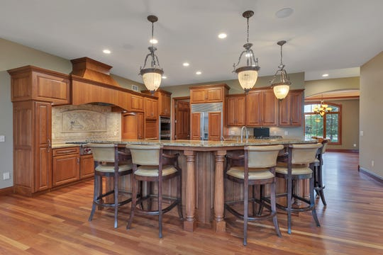 Cherry cabinetry abounds in the kitchen, a large island offers bar stool seating for six and is the perfect place for guests to mingle.