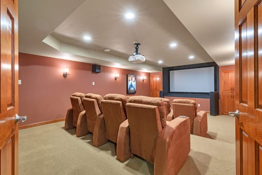 A theater room with leveled seating can be accessed from the family room through a pair of French doors.