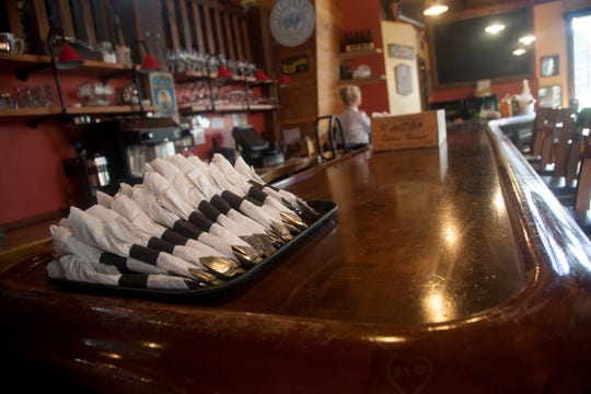 Employees at George's Corner roll utensils in preparation to reopen to dine-in patrons Thursday, April 30, 2020.