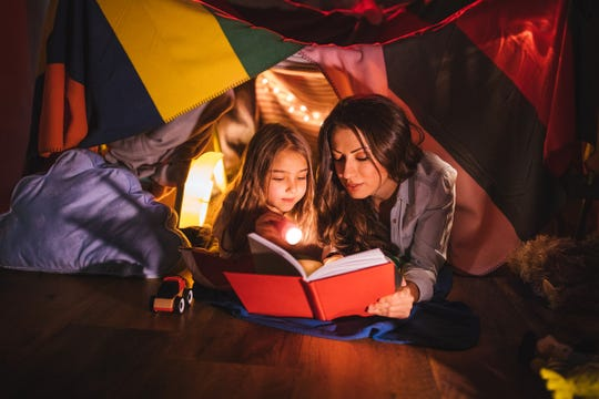 A mother and daughter read under a blanket fort at night
